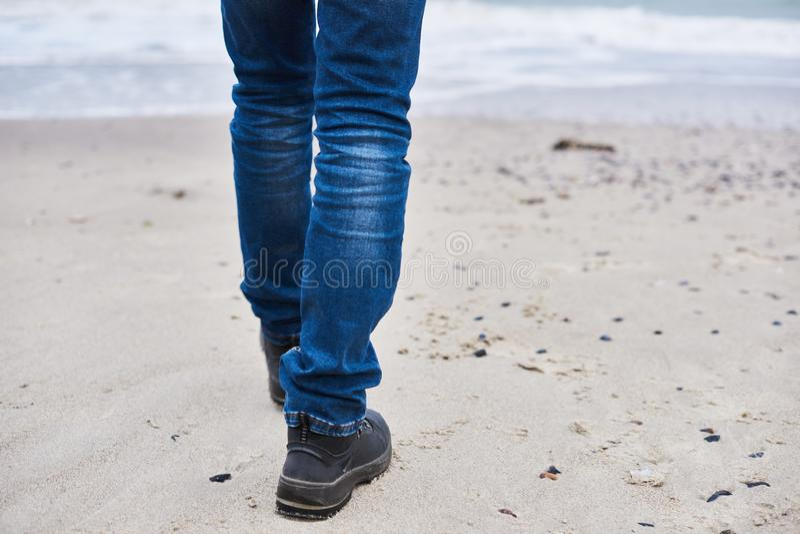 Un uomo fa una passeggiata lungo la spiaggia Gli uomini indossano le scarpe ed i jeans camminano fuori immagini stock