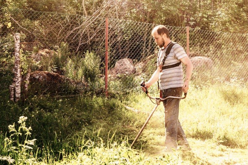 Un uomo falcia l'erba nel suo giardino con un regolatore immagine stock