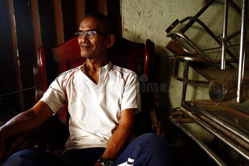 Un uomo filippino maturo si siede su una sedia e sulle pose per la macchina fotografica fotografia stock