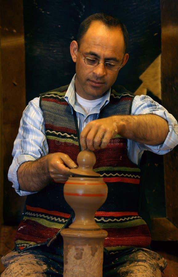 Un uomo forma il coperchio di una pentola in ceramica fotografia stock libera da diritti