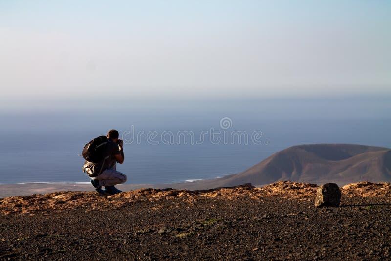Un uomo fotografa un'isola nell'oceano, occupante sull'orlo di una scogliera immagini stock