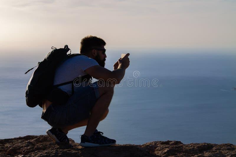 Un uomo fotografa un'isola nell'oceano, occupante sull'orlo di una scogliera immagine stock