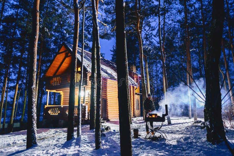 Un uomo frigge la carne arrostita contro lo sfondo del cottage i fotografia stock libera da diritti