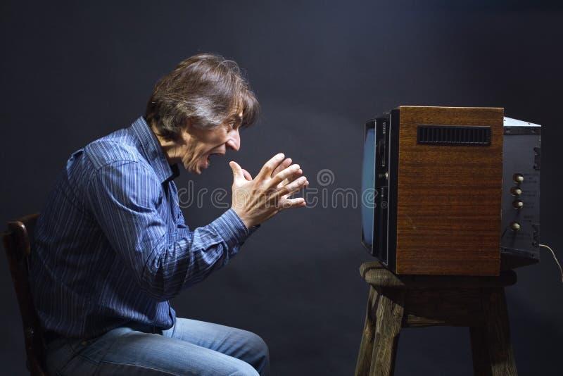 Un uomo grida mentre guarda la TV. fotografia stock libera da diritti