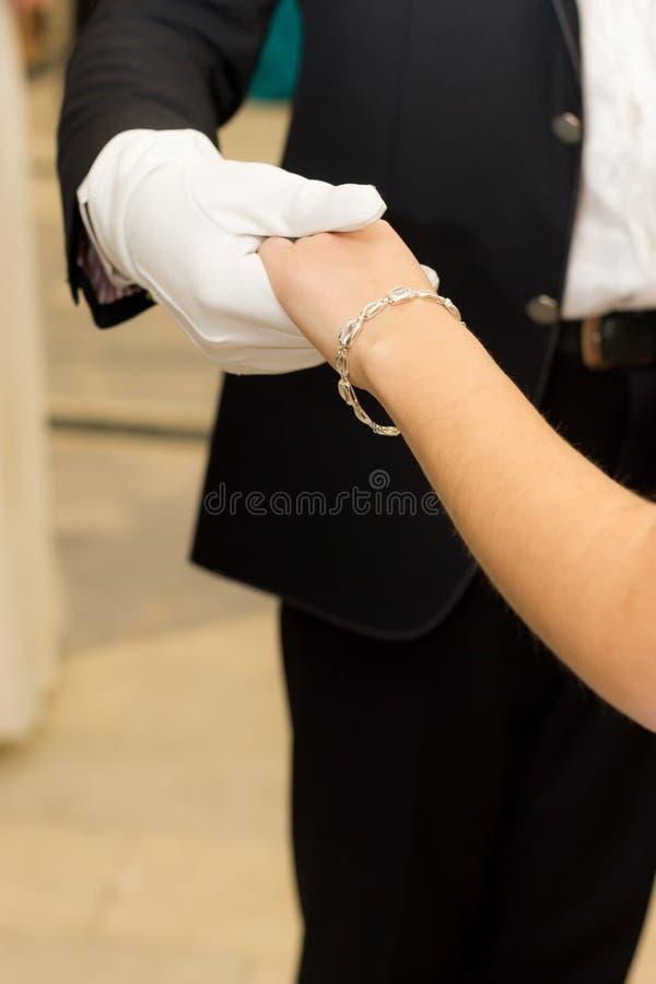 Un uomo in un guanto bianco che tiene delicatamente la mano di una ragazza immagine stock