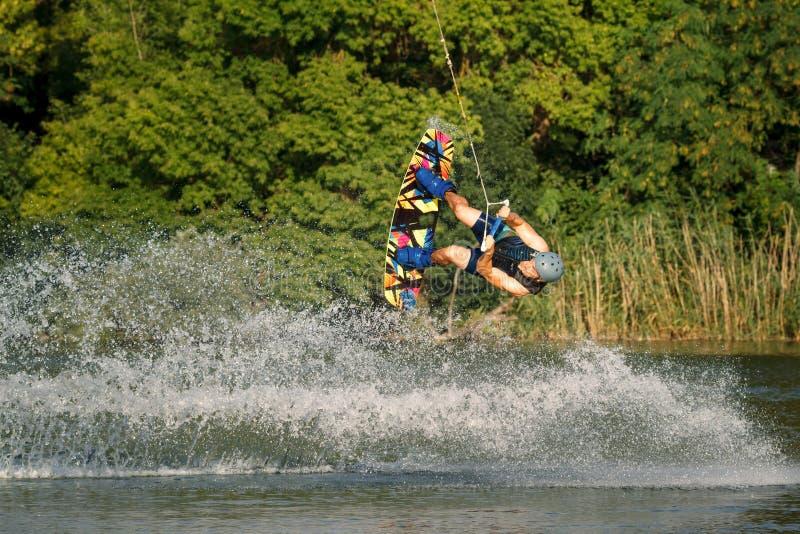Un uomo impegnato in wakeboard sul lago esegue i salti fotografia stock