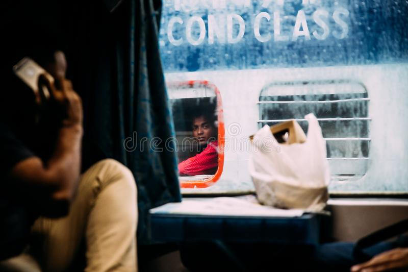 Un uomo indiano che fissa da un altro treno mentre piovendo fuori dalla stazione ferroviaria in Calcutta, India della giunzione d fotografia stock libera da diritti