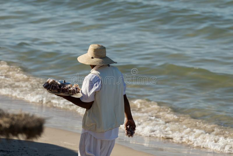 Un uomo indigeno con un cappello vende i dadi sulla spiaggia immagini stock