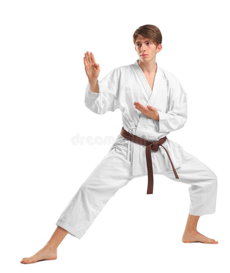 Un uomo in un kimono in una posizione di combattimento su un fondo bianco isolato fotografia stock