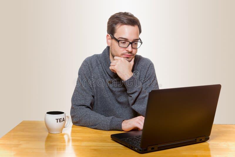 Un uomo lavora ad un computer portatile mentre si siede fotografia stock