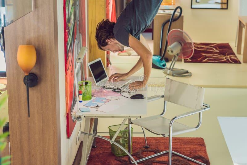 Un uomo lavora al computer sottosopra fotografia stock libera da diritti