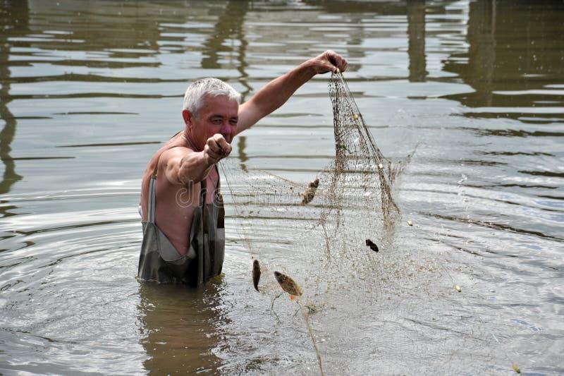 Un uomo locale sta pescando con una rete durante l'inondazione nel giardino fotografia stock libera da diritti