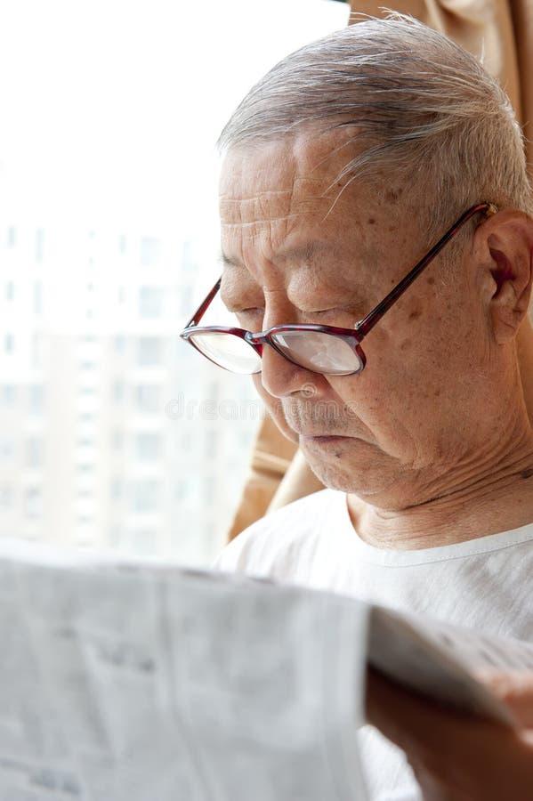 Un uomo maggiore sta leggendo fotografia stock libera da diritti