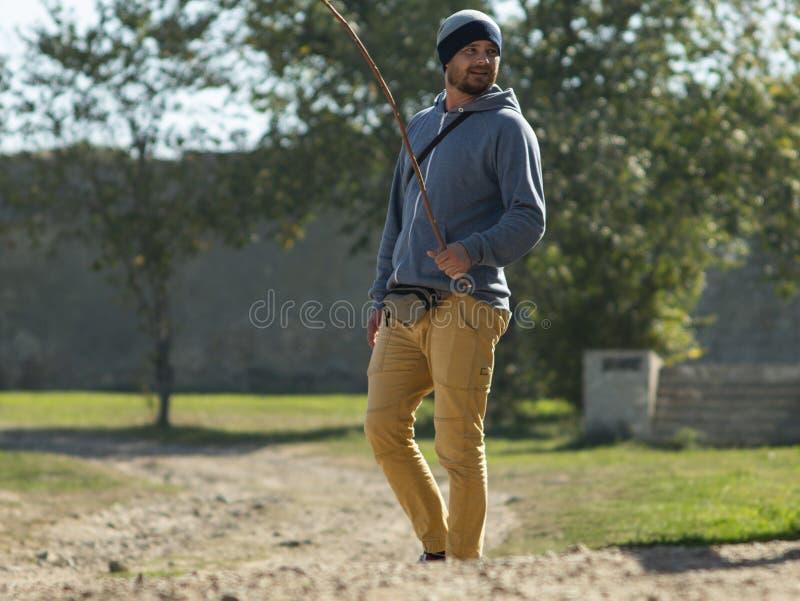 Un uomo in un maglione incappucciato ed in un cappello tricottato sta stando contro un fondo degli alberi verdi con un bastone e  immagini stock libere da diritti