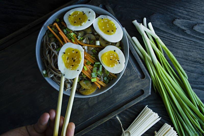 Un uomo mangia le tagliatelle di soba del grano saraceno con salsa ed i piatti laterali in brodo Alimento giapponese Cucina asiat immagine stock