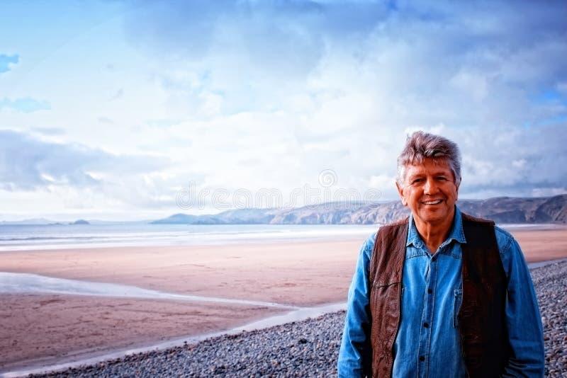Un uomo maturo che sta sulla spiaggia di Newgale fotografie stock