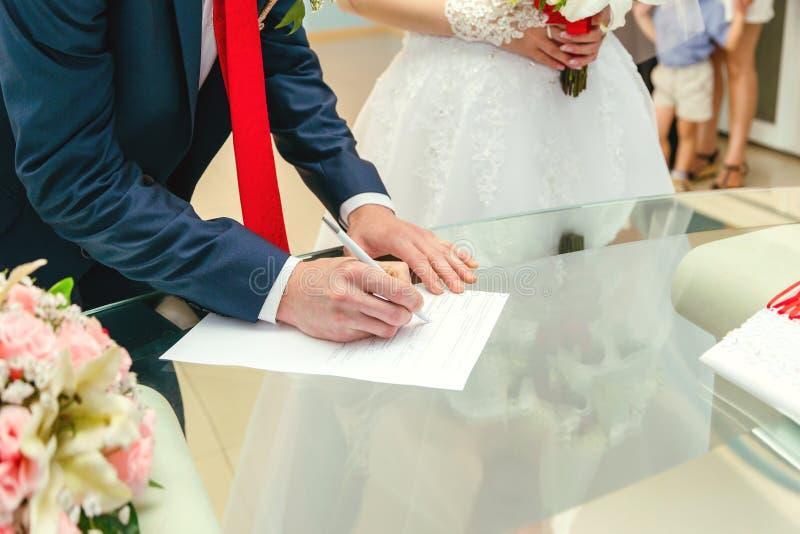 Un uomo mette una firma nei documenti mani e documenti di un uomo fotografia stock libera da diritti