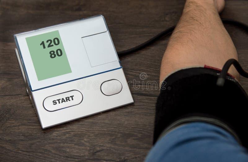 Un uomo misura la sua pressione con un pripore fotografie stock