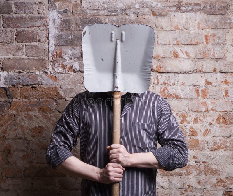 Un uomo nasconde il suo fronte dietro una pala. fotografia stock libera da diritti