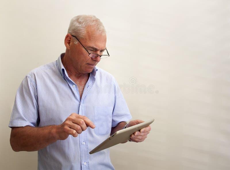 Un uomo nel suo 60s con una compressa del pc in sua mano fotografie stock libere da diritti