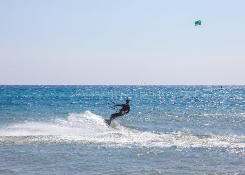 Un uomo nel vestito pieno dell'ingranaggio sopra l'oceano L'atleta tenendo costante la maniglia mentre scivolando nel mare Imbarc immagini stock