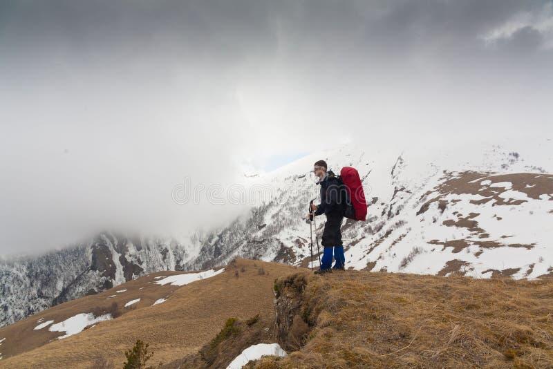 Un uomo nell'inverno di giorno della montagna unico fotografia stock