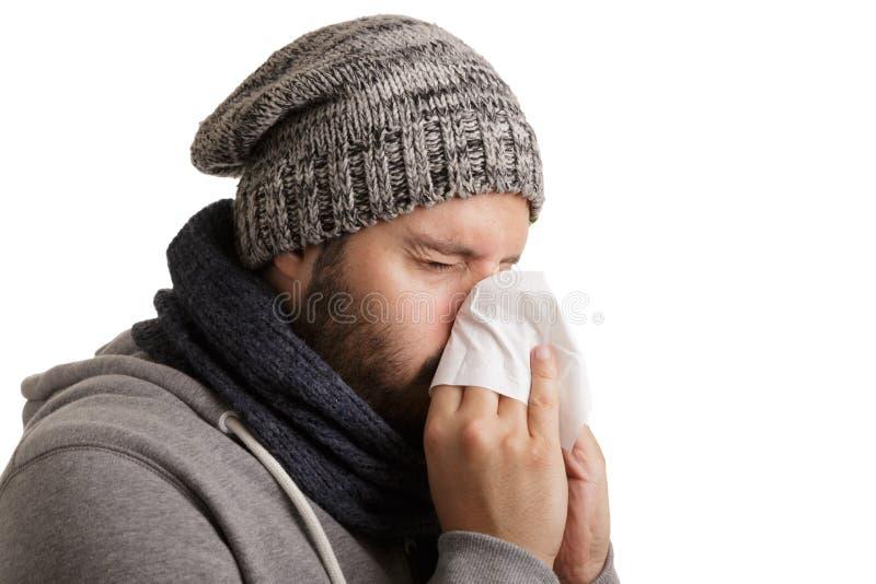 Un uomo nell'orario invernale con la malattia deve starnutire e soffiare in un fazzoletto isolato su fondo bianco fotografia stock