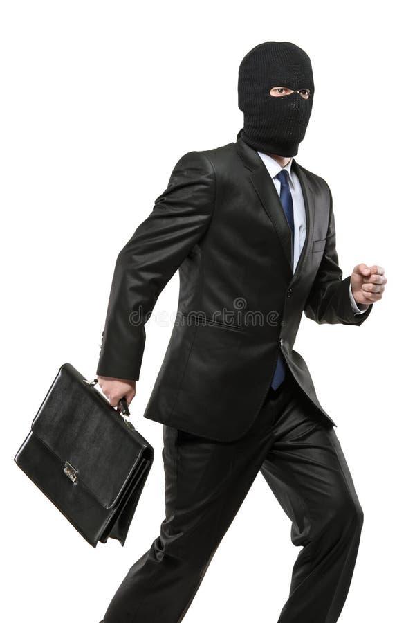 Un uomo nella mascherina di furto che trasporta una cartella fotografia stock libera da diritti