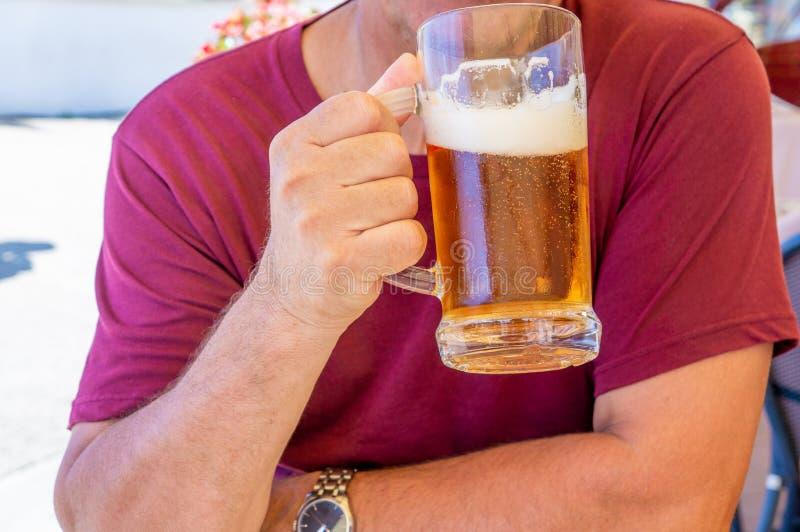 Un uomo non identificato beve da una grande tazza di vetro della birra leggera sui precedenti di un pub su una tavola di legno fotografie stock