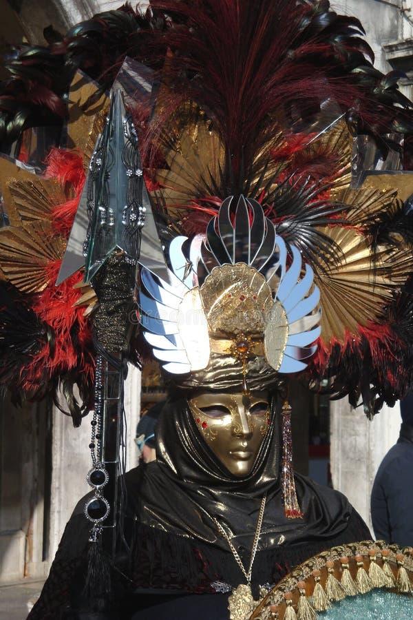 Un uomo non identificato ed i vestiti vestiti operati elaborati con oro maschera, cappello rosso e nero della piuma durante il ca immagini stock
