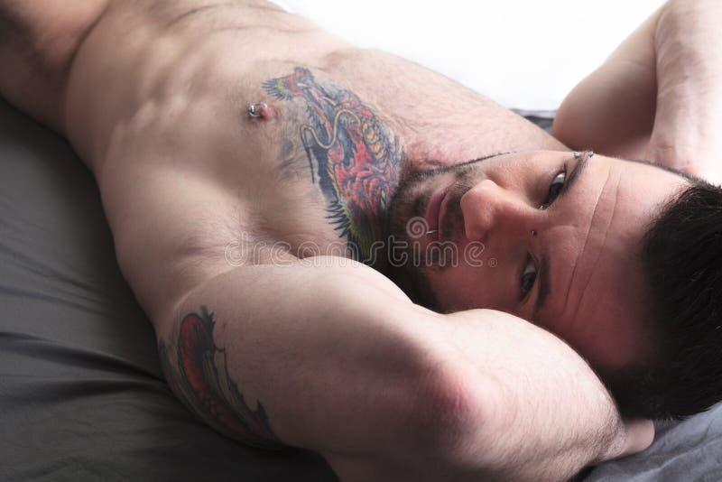 Un uomo nudo sexy risiede nel letto immagine stock