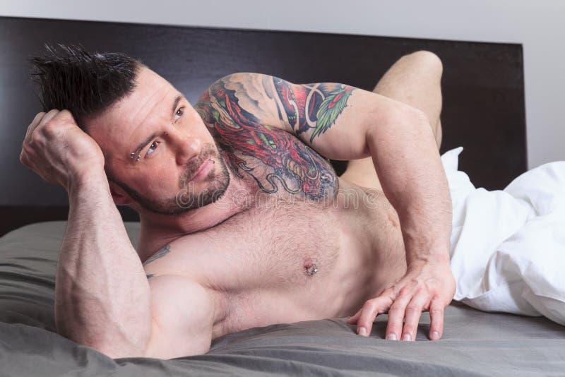 Un uomo nudo sexy risiede nel letto immagine stock libera da diritti