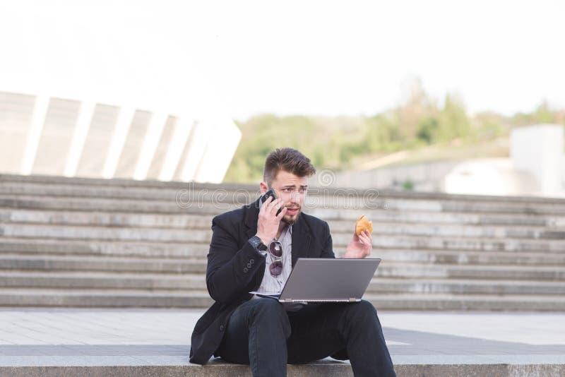 Un uomo occupato in un vestito si siede sui computer portatili con un computer portatile sul suo rivestimento, mangia un panino e immagine stock