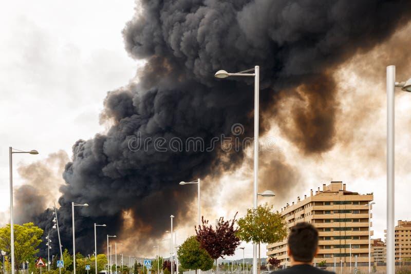 Un uomo osserva un fumo denso e scuro da un fuoco fotografie stock libere da diritti