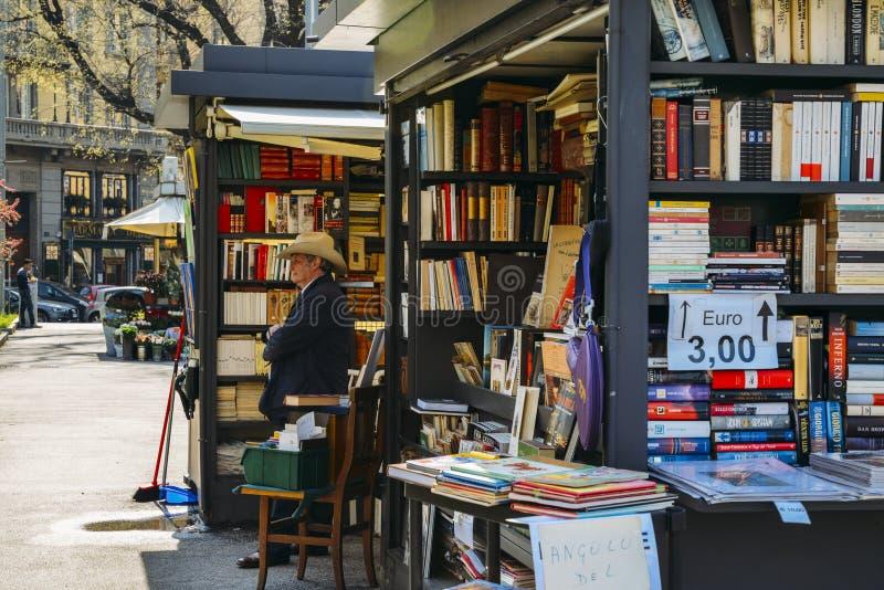 Un uomo più anziano con un cappello da cowboy vende i libri sulla via fotografie stock