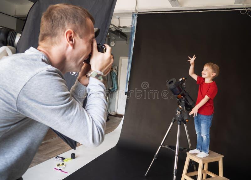 Un uomo porta un ritratto di un ragazzo con un telescopio in studio con luce artificiale su uno sfondo nero immagini stock