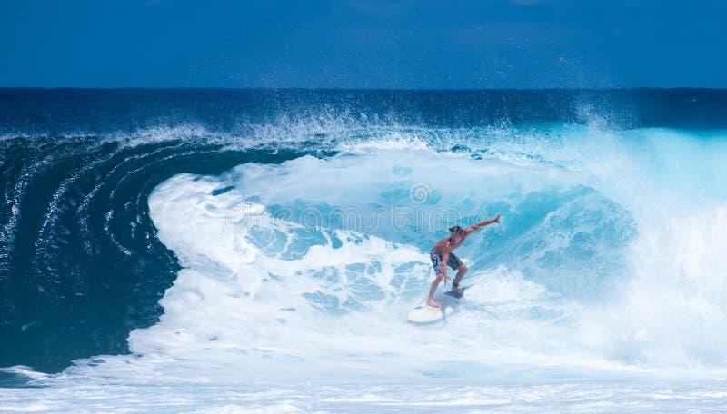 Un uomo pratica il surfing il barilotto di un 10' onda immagine stock
