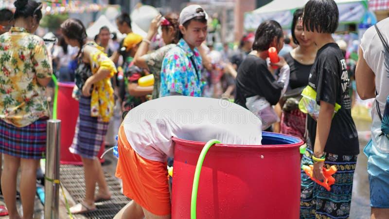 Un uomo prova ad ottenere l'acqua nel carro armato nel festival di Songkran fotografia stock