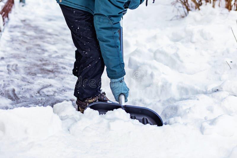 Un uomo pulisce la neve vicino alla casa con una grande pala nera fotografia stock