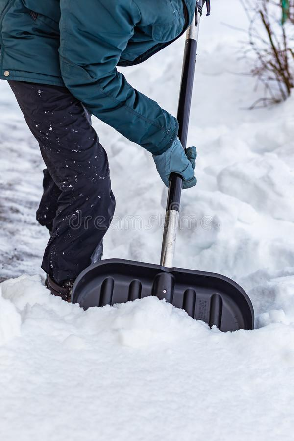 Un uomo pulisce la neve vicino alla casa con una grande pala nera immagini stock libere da diritti