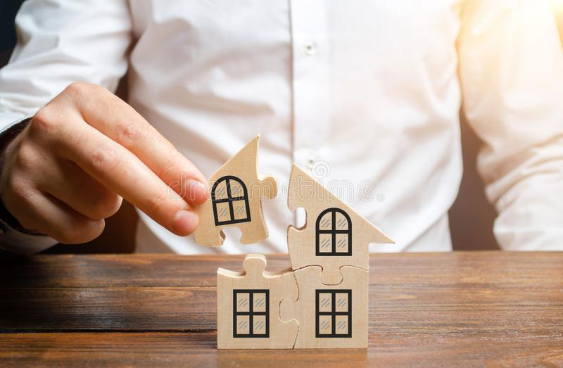 Un uomo raccoglie una casa dei puzzle Costruzione del vostro proprio edificio residenziale Mutuo ipotecario, espansione residenzi fotografia stock libera da diritti