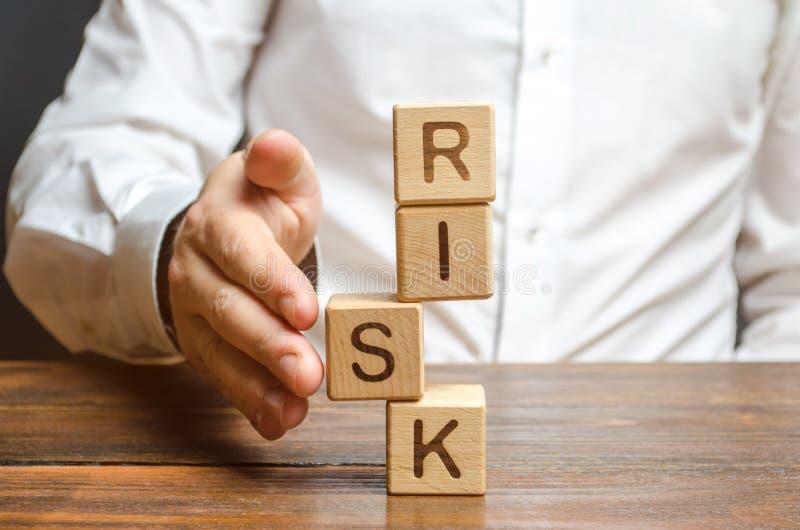 Un uomo raddrizza un segmento in una torre instabile dei cubi identificati rischio Gestione dei rischi, valutazione di costo ed a fotografia stock