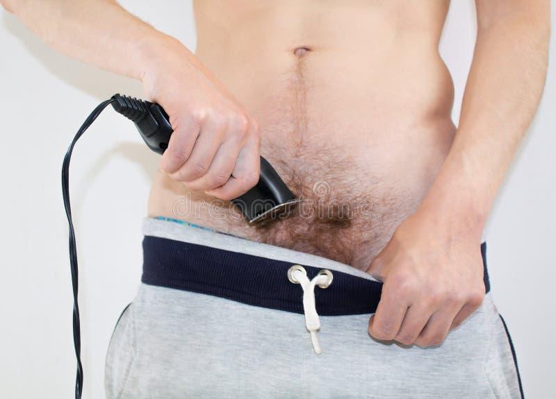 Un uomo rade un pube con un rasoio elettrico fotografia stock libera da diritti