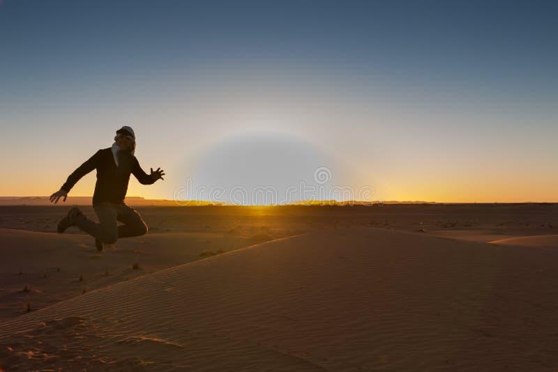Un uomo retroilluminato salta felicemente nel deserto di ERG Chebbi all'alba immagine stock