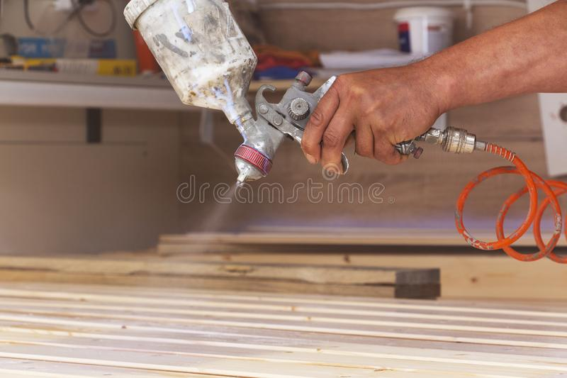 Un uomo riguarda i bordi di legno di vernice nell'officina con uno spruzzo fotografie stock libere da diritti