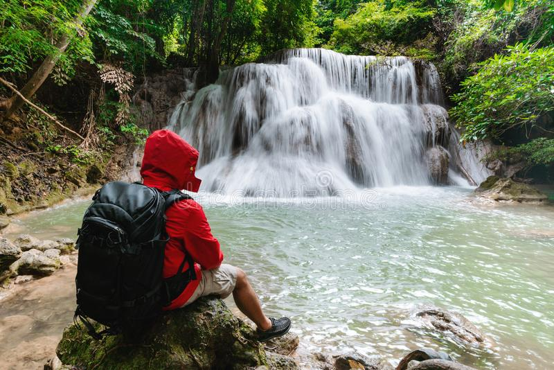 Un uomo in rivestimento rosso con lo zaino che si siede sulla roccia che gode di bella cascata in foresta pluviale tropicale Huay fotografie stock