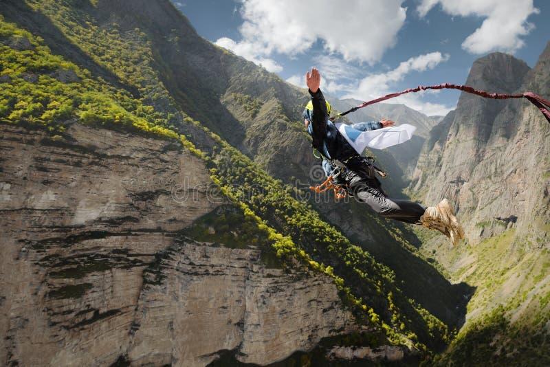 Un uomo in un ropeup di salti del casco con una bandiera vuota nelle montagne Sport estremi svago immagine stock libera da diritti