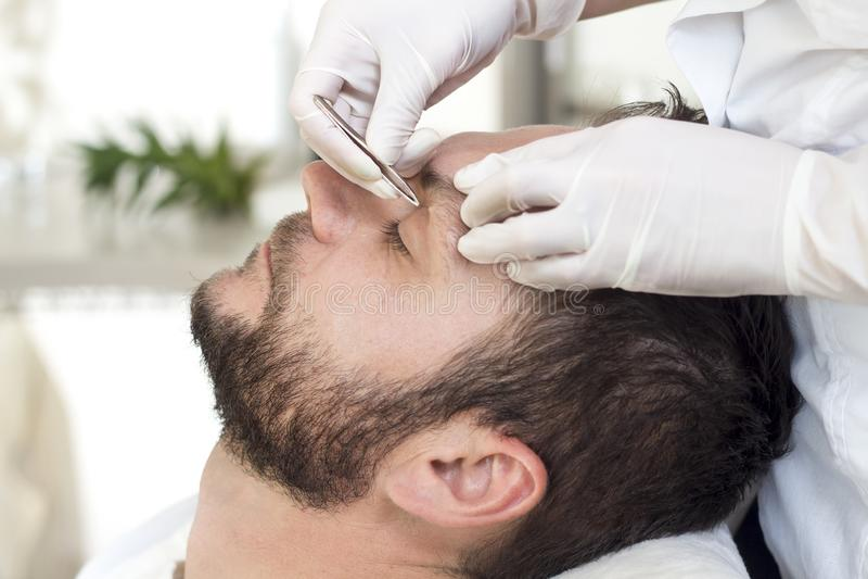 Un uomo in un salone di bellezza durante la procedura di adeguamento del sopracciglio immagini stock libere da diritti