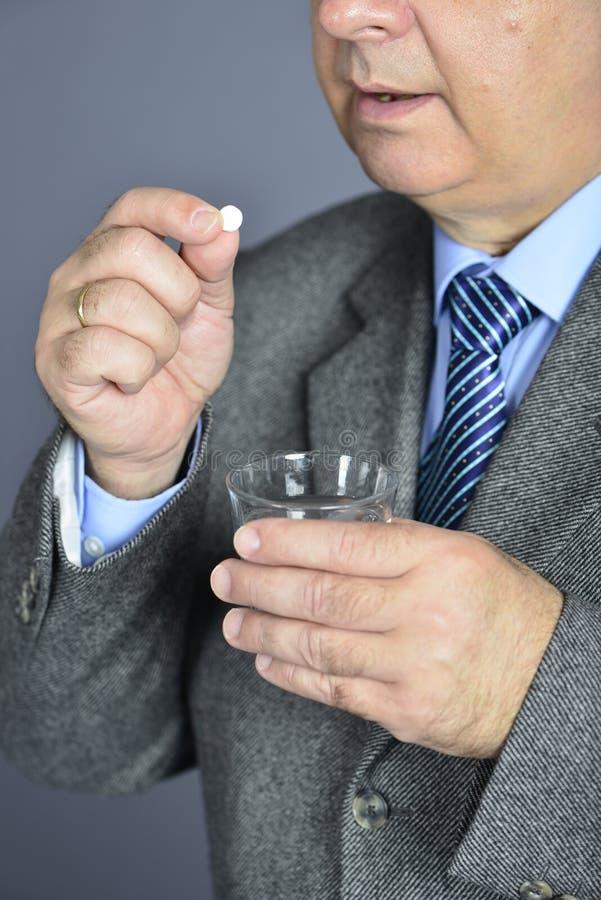 Un uomo senior che prende medicina con un bicchiere d'acqua immagini stock libere da diritti