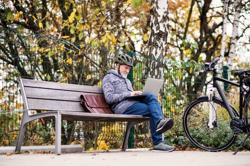 Un uomo senior con electrobike che si siede su un'aria aperta del banco in città, facendo uso del computer portatile immagine stock